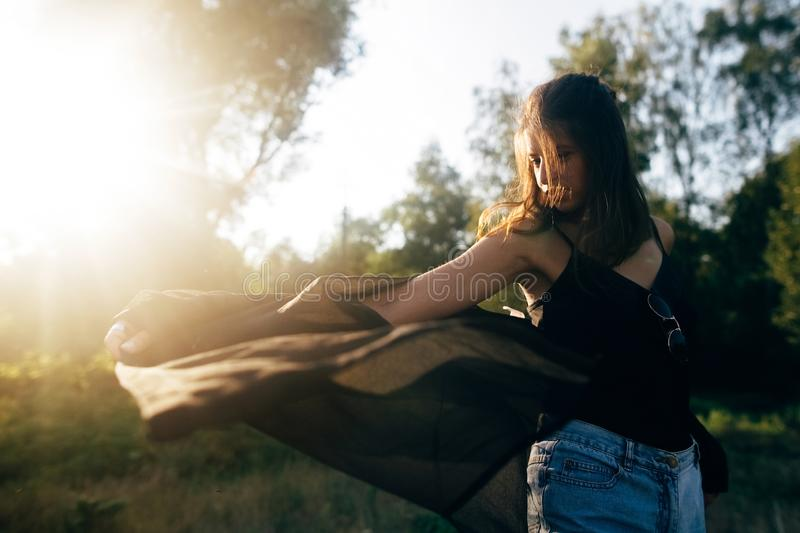 Stylish hipster girl having fun in sunny park in amazing sunbeams, atmospheric moment. Fashionable cool woman dancing and moving. In evening light. Selective royalty free stock image