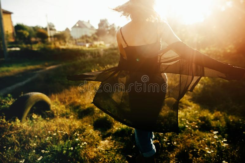 Stylish hipster girl having fun in sunny park in amazing sunbeams, atmospheric moment. Fashionable cool woman dancing and smiling. In evening light. Selective stock photos