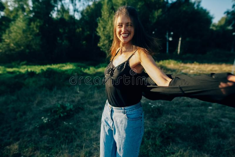 Stylish hipster girl having fun in sunny park in amazing sunbeams, atmospheric moment. Fashionable cool woman dancing and smiling. In evening light. Selective stock photo