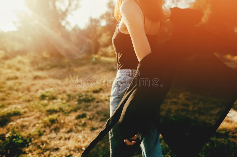 Stylish hipster girl having fun in sunny park in amazing sunbeams, atmospheric moment. Fashionable cool woman dancing and smiling. In evening light. Selective royalty free stock photo