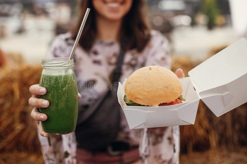 Stylish hipster girl holding delicious vegan burger and smoothie in glass jar in hands at street food festival, close up. Happy stock photo