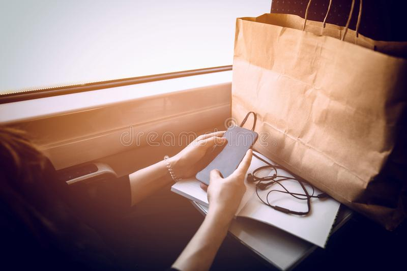 stylish hipster girl holding phone with headphones at window light in train. beautiful young woman looking at smartphone empty sc royalty free stock images