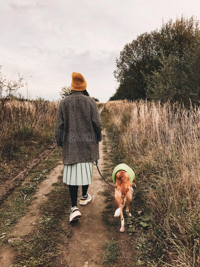 Free Stylish Hipster Girl In Yellow Hat And Coat Walking With Her Golden Dog In Coat In Autumn Field Among Herbs. Woman In Modern Stock Photo - 161257870