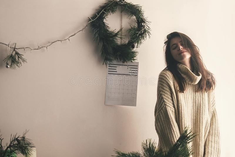 Stylish hipster girl in knitted sweater posing in rustic room on stock photography