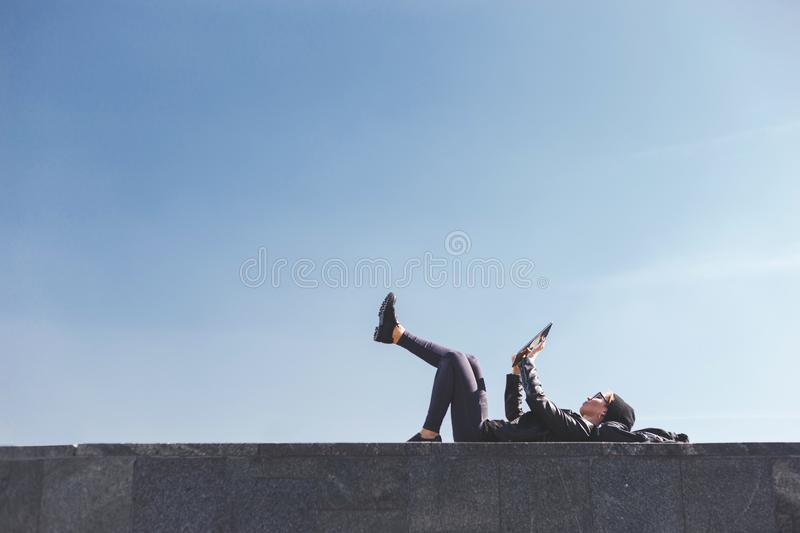 A stylish hipster girl lies on her back with her legs raised on a parapet and uses a tablet. Urban fashion, modern youth royalty free stock image