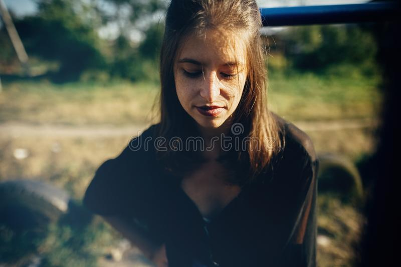 Stylish hipster girl posing in sunny street, atmospheric moment. Fashionable cool woman smiling and relaxing in evening light. Selective focus. Retro effect royalty free stock photo