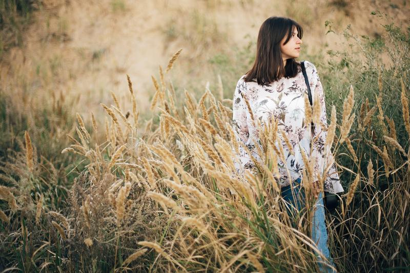 Stylish hipster girl posing at wildflowers, long herbs on beach and cliff near sea. Summer vacation. Portrait of happy calm boho stock image