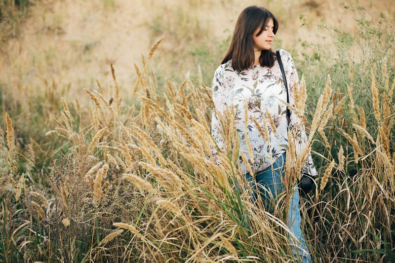 Stylish hipster girl posing at wildflowers, long herbs on beach and cliff near sea. Summer vacation. Portrait of happy calm boho royalty free stock image