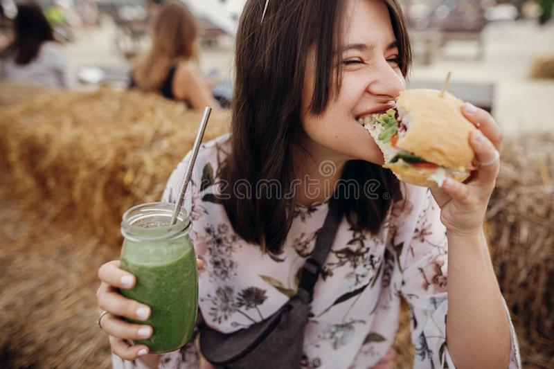Stylish hipster girl in sunglasses eating delicious vegan burger and holding smoothie in glass jar in hands at street food stock photo