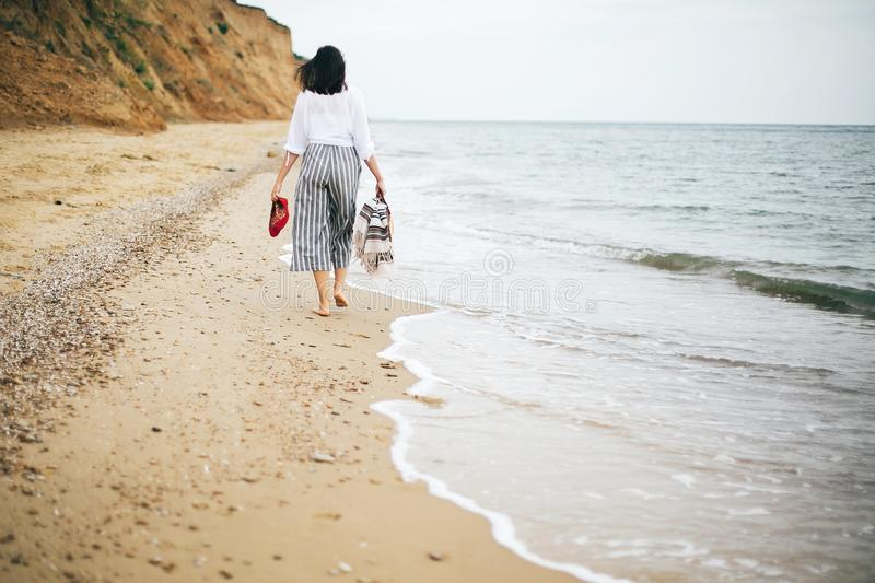 Stylish hipster girl walking barefoot on beach, holding bag and shoes in hand. Happy boho woman relaxing at sea, enjoying walk on stock photography