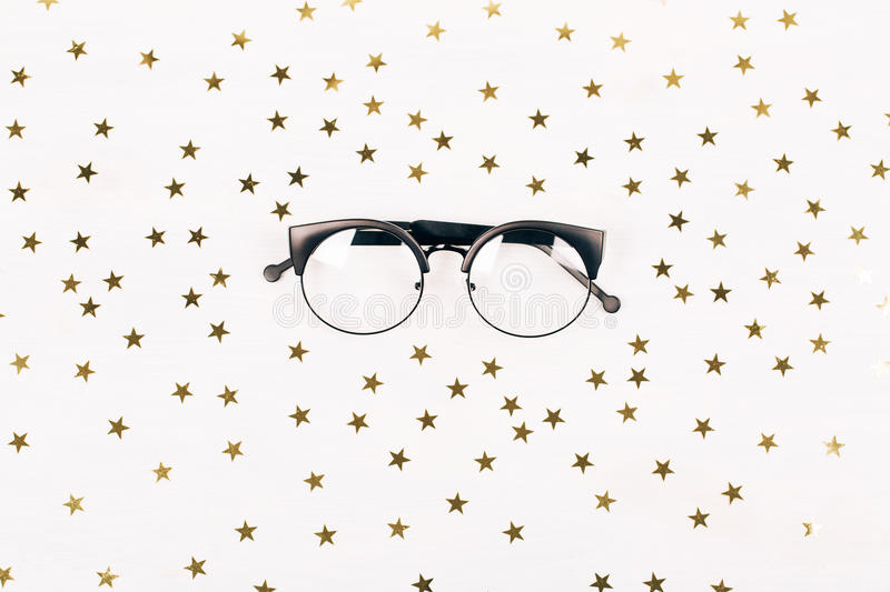 Stylish hipster glasses on glamorous white background. Stylish hipser glasses on glamorous white background with golden sparkling stars. Flat lay royalty free stock image