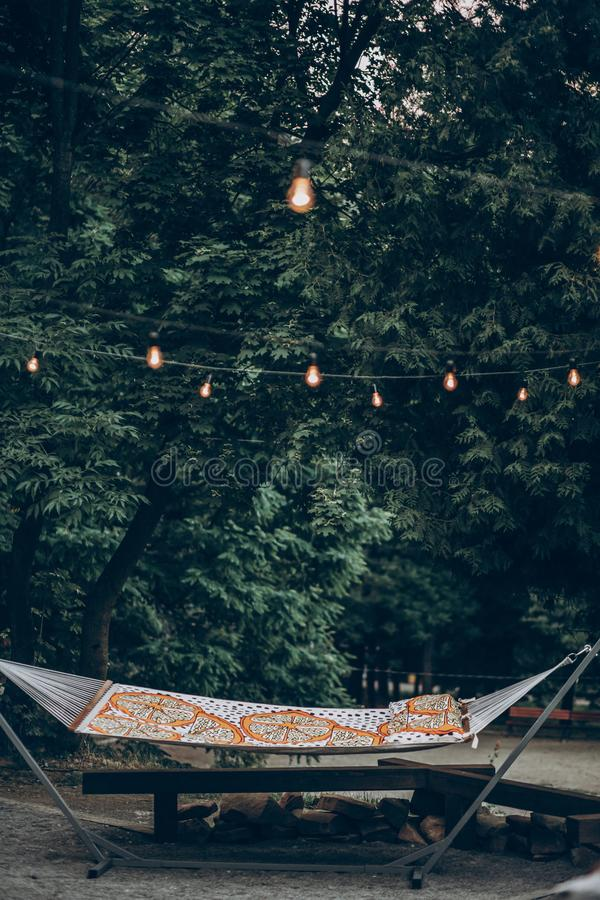 Stylish hipster hammock under romantic lights in park at resort, family camping trip concept stock image