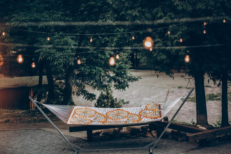 Stylish hipster hammock under romantic lights in park at resort, family camping trip concept royalty free stock photo