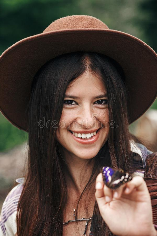 stylish hipster,happy woman in hat holding apatura iris on fingers in forest in mountains. beautiful butterfly on girl hand. stock photos