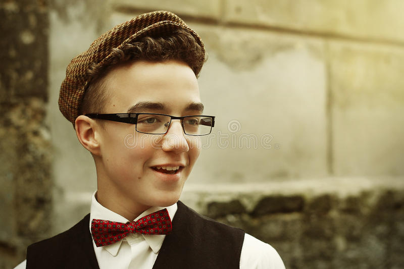 Stylish hipster man smiling with confidence, funny emotions on b. Ackground of old city street wall royalty free stock image