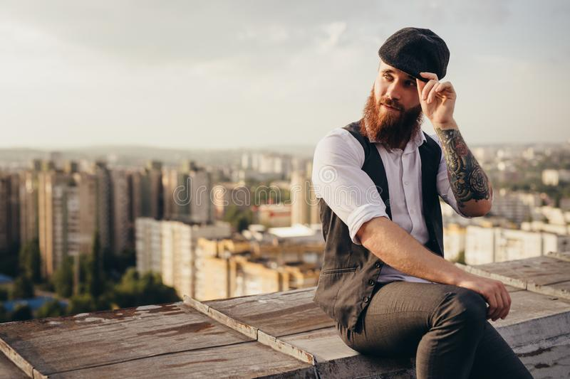 Stylish hipster resting on rooftop royalty free stock images
