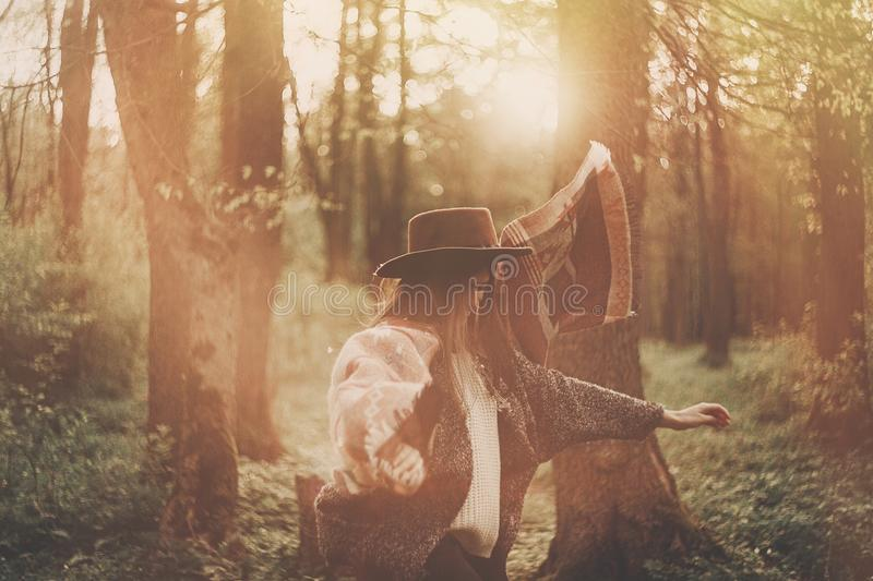 Stylish hipster traveler girl in hat exploring in woods in amazing evening sunshine light. woman having fun and jumping in. Sunlight. space for text stock images