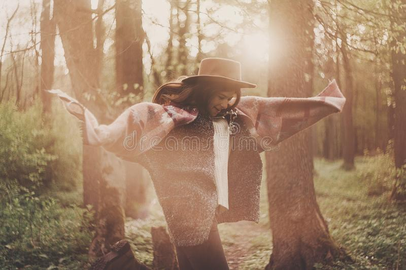 Stylish hipster traveler girl in hat exploring in woods in amazing evening sunshine light. woman having fun and jumping in. Sunlight. space for text royalty free stock images