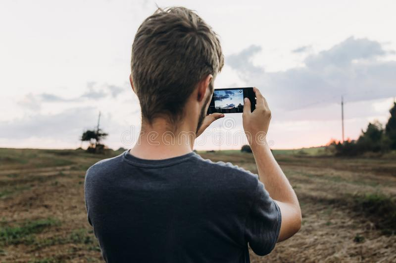 Stylish hipster traveler holding smart phone taking photo of beautiful sunset landscape in summer field. instagram photography. e. Xploring and discovering stock image