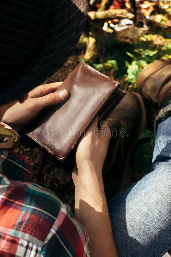 Stylish hipster traveler holding tobacco and pipe in sunny fores stock images