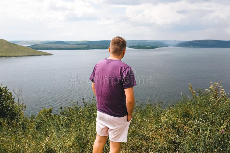 Stylish hipster traveler in purple shirt standing on top of rock mountain with amazing view on river. Young brutal guy exploring royalty free stock photos