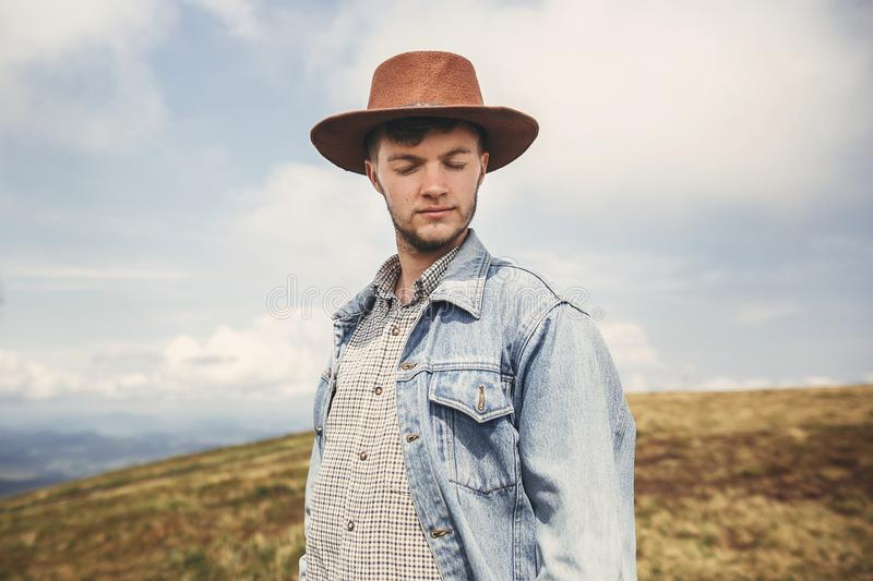 Stylish hipster traveler relaxing on top of sunny hills on background of mountains. Copy space. Handsome man in hat traveling in royalty free stock photo