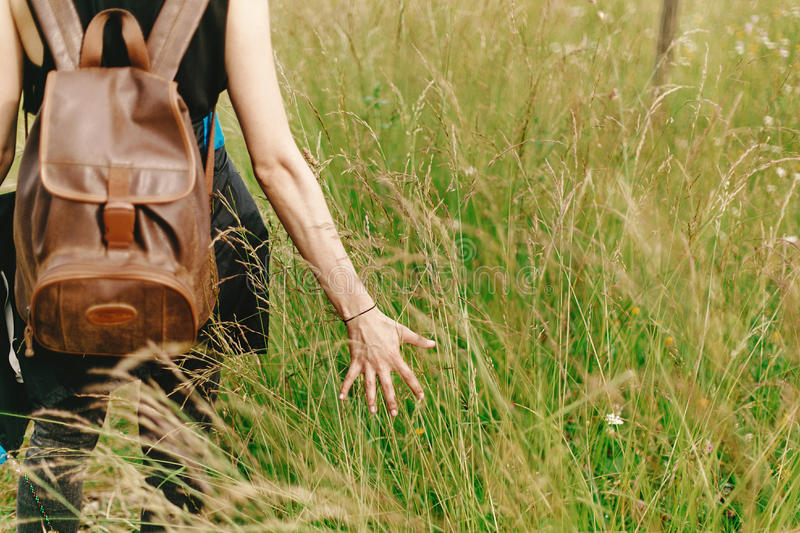 Stylish hipster traveler walking in grass and holding in hand h. Erb wildflowers in summer mountains, peaceful relaxing moment, space for text stock images