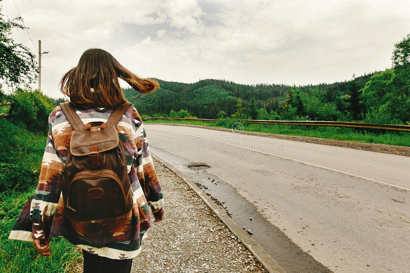 stylish hipster woman with backpak walking and looking at mountains, summer travel concept, space for text royalty free stock photo