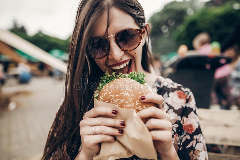 Stylish hipster woman eating juicy burger. boho girl biting cheeseburger, smiling at street food festival. summertime. summer vac. Ation travel picnic. space for royalty free stock image