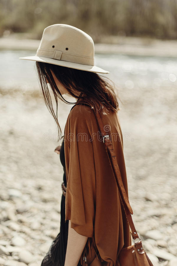 stylish hipster woman in hat, fringe poncho walking on river beach. boho traveler girl in gypsy look, summer travel. atmospheric royalty free stock photography