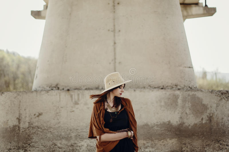Stylish hipster woman in hat with windy hair posing near river s. Tones. boho traveler girl in gypsy look. summer travel. atmospheric moment. space for text stock images
