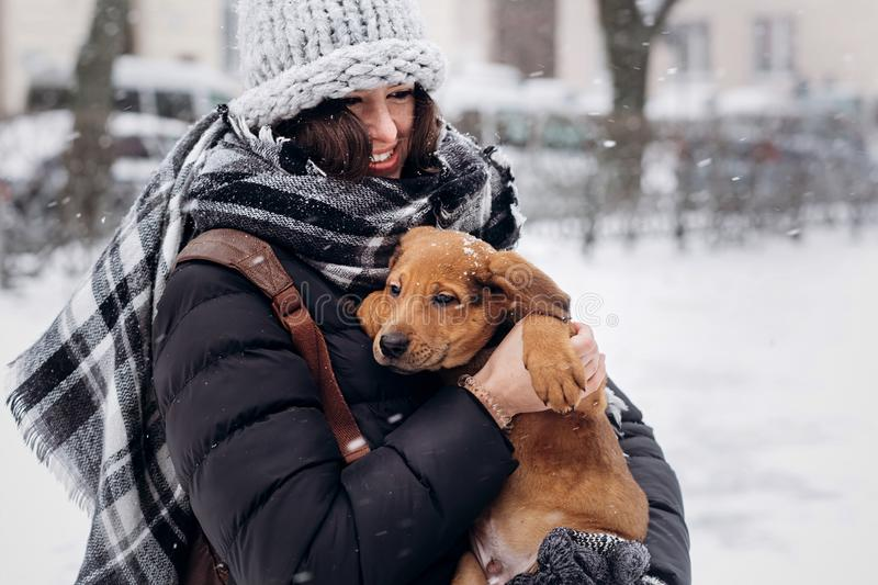 Stylish hipster woman hugging and smiling cute puppy in snowy co. Ld winter park and caressing. moments of true happiness. adoption concept. save animals stock images