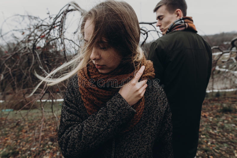 Stylish hipster woman and man posing in windy autumn park. sensual atmospheric moment with space for text. fashionable cool. Stylish hipster women and men posing royalty free stock image