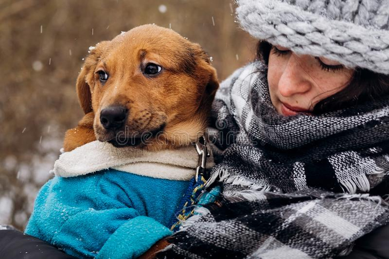 stylish hipster woman playing with cute puppy in snowy cold winter park and caress. moments of true happiness. adoption concept. stock photo