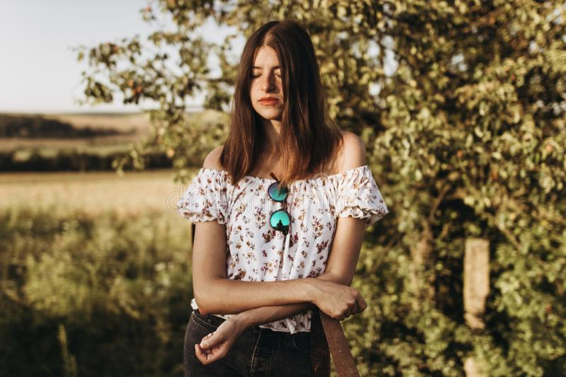 Stylish hipster woman relaxing in evening under sunlight in summer field. girl traveling in boho dress. tender sensual portrait i. N sunshine stock image