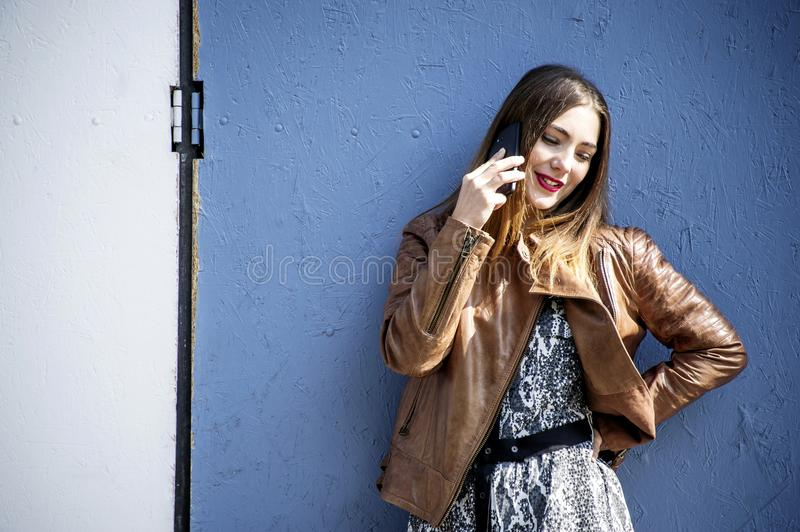 Stylish hipster woman is talking on her mobile in front of a blue wall background. royalty free stock photography