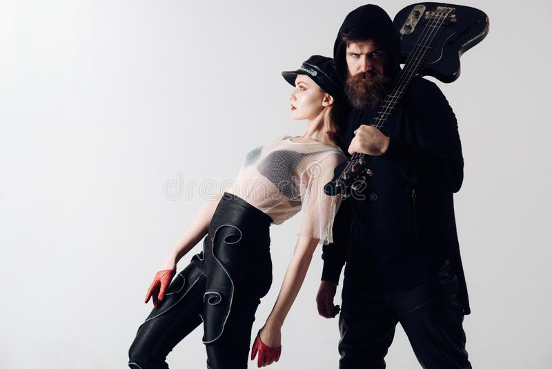 Stylish hipster and woman together with electric guitar. Rock couple of girl and bearded man with guitar. cool rock royalty free stock photography