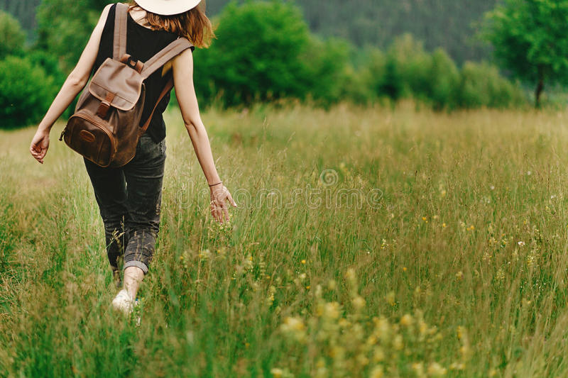Stylish hipster woman walking in grass and holding in hand herb. Wildflowers in summer mountains, travel concept, peaceful relaxing moment royalty free stock photo
