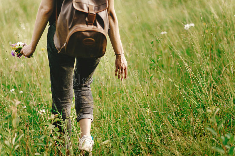 Stylish hipster woman walking in grass and holding in hand herb stock photography