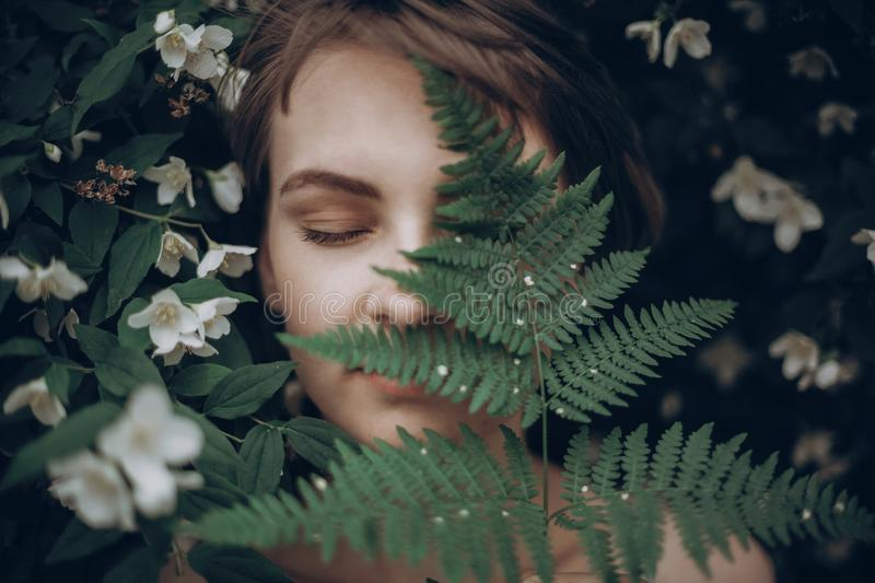 Stylish hipster woman with fern leaf embracing. girl portrait wi stock images