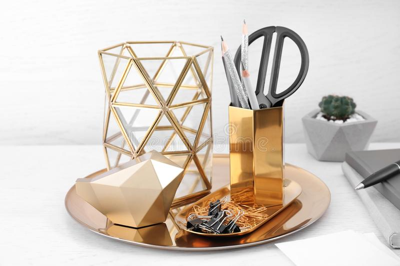 Stylish holder for stationery with office supplies and decorative elements on wooden table. Stylish holder for stationery with office supplies and decorative stock image