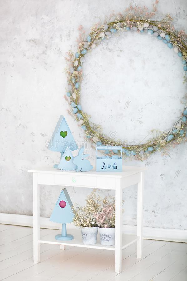Stylish home decor in blue is a wooden basket, decorative nesting boxes and a cute rabbit. Easter decorations. Summer village comp. Osition with a wooden nesting royalty free stock image