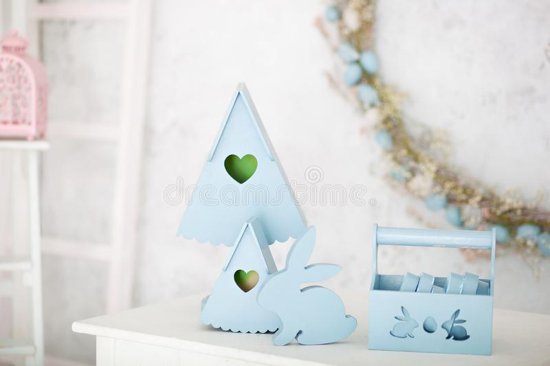 Stylish home decor in blue is a wooden basket, decorative nesting boxes and a cute rabbit. Easter decorations. Summer village comp. Osition with a wooden nesting royalty free stock photo