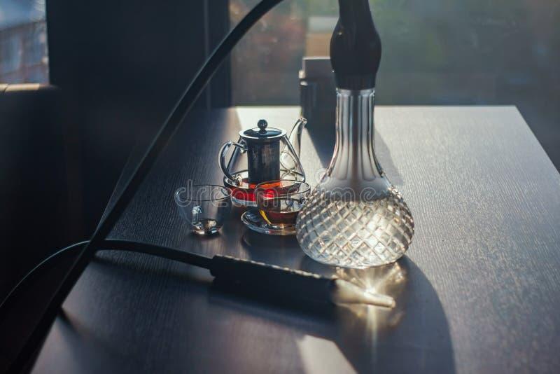 Stylish hookah glass and tea kettle. Smoke royalty free stock image