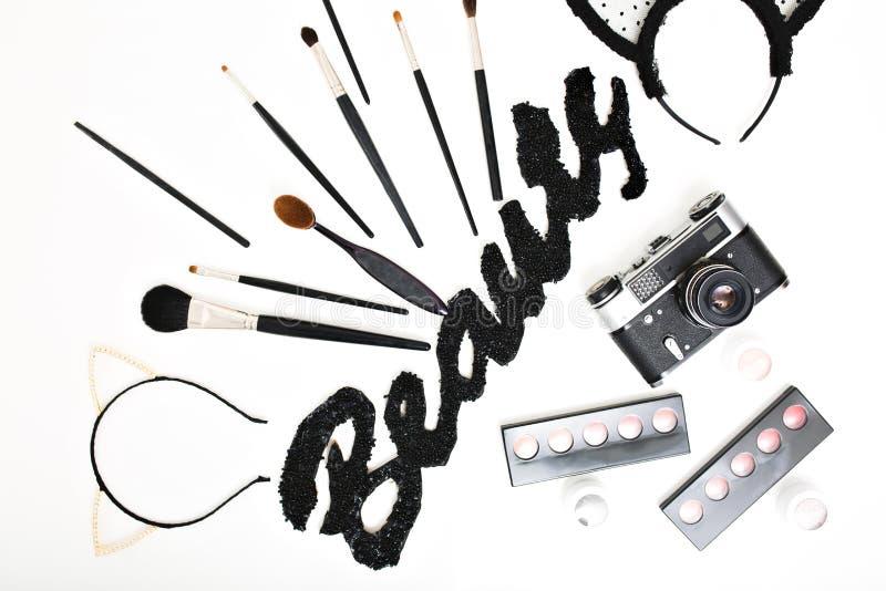 Stylish image of makeup stuff above on white background. Black inscription Beauty , brushes, glamour set, cosmetic royalty free stock photography