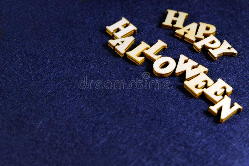 Words of wooden letters. Stylish inscription HAPPY HALLOWEEN on a dark blue background in the upper right corner of the frame. Cop. Stylish inscription HAPPY royalty free stock photo