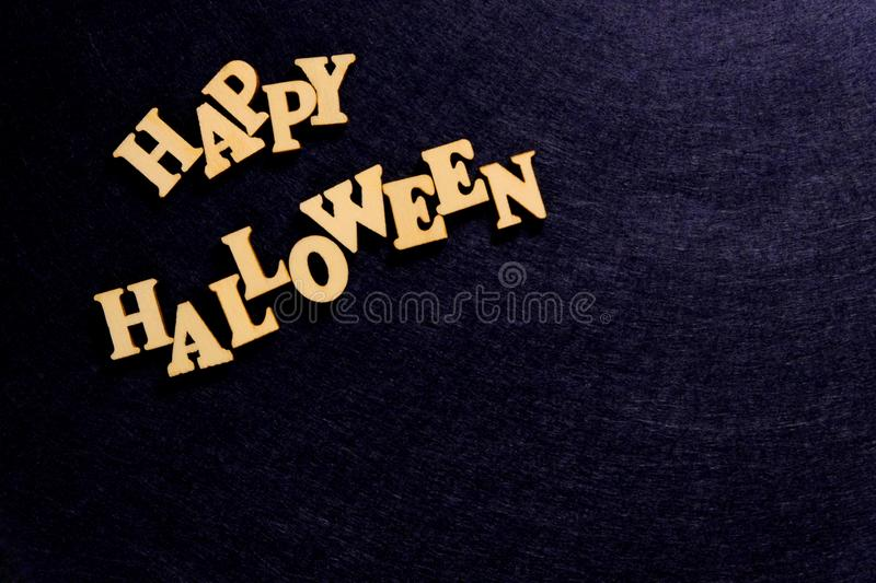 Stylish inscription HAPPY HALLOWEEN on a dark blue background. Words of wooden letters. Copy space. Words of wooden letters. Stylish inscription HAPPY HALLOWEEN royalty free stock image