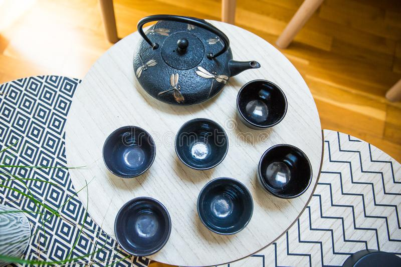 Stylish Interior Decoration of a Cast Iron Teapot with Dragonfly Decoration and Round Cups on Geometric Tables. Stylish Interior Decoration of a Cast Iron Teapot stock photography