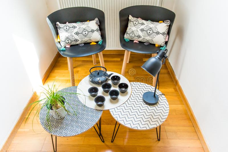 Stylish Interior Decoration of a Cosy Corner of a House with Cast Iron Teapot, Cups, Geometric Tables and Chairs. Stylish Interior Decoration of a Cosy Corner of royalty free stock photos