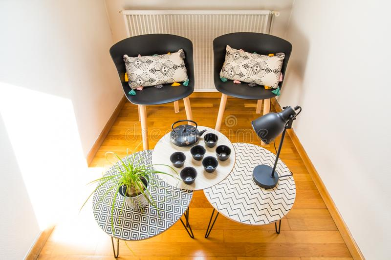 Stylish Interior Decoration of a Cosy Corner of a House with Cast Iron Teapot, Cups, Geometric Tables and Chairs. Stylish Interior Decoration of a Cosy Corner of stock photography
